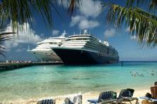 Två stora kryssningsfartyg med strand och palmer i förgrunden